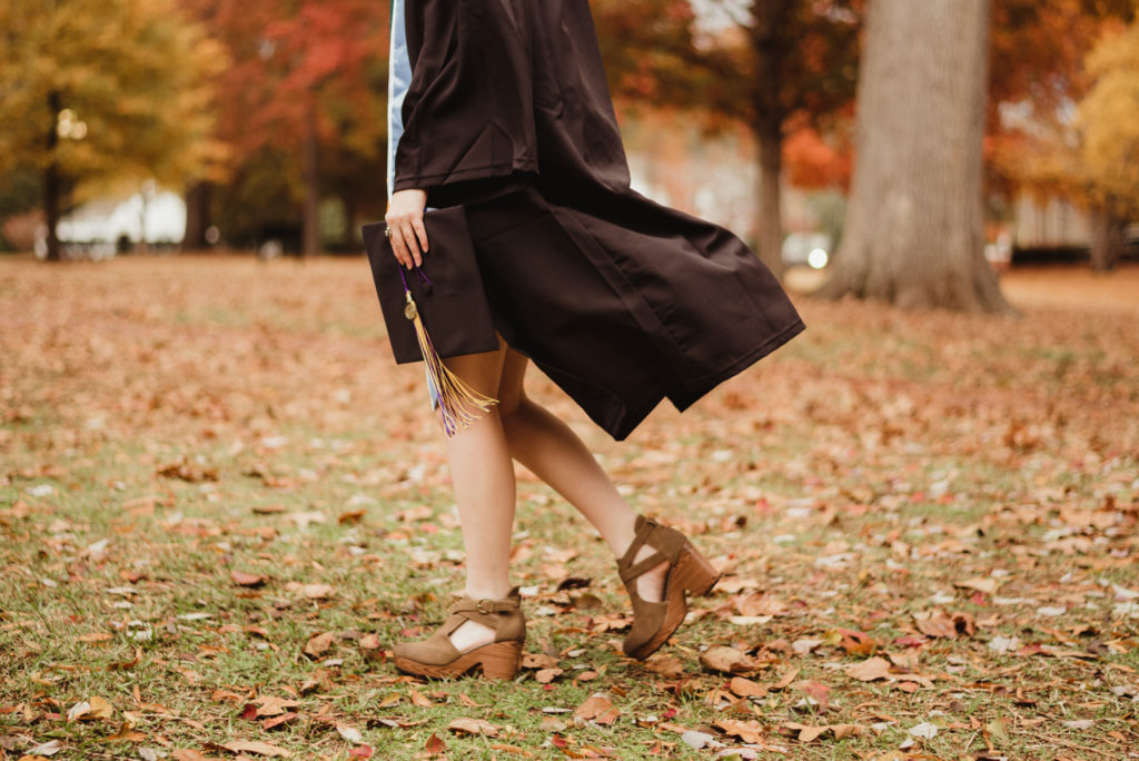 Lower half of individual in graduate gown, holding their cap and walking across a leaf covered lawn.