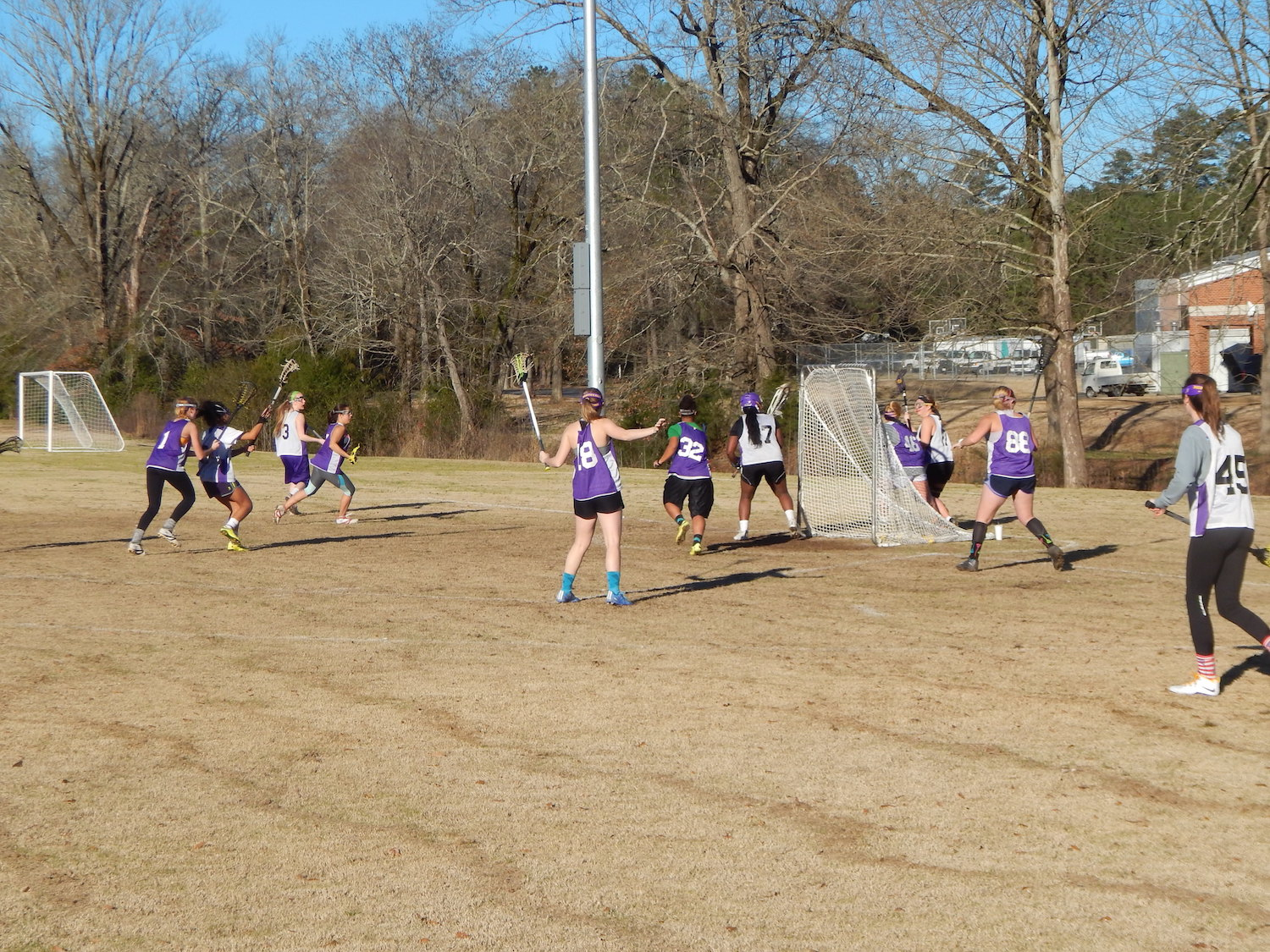 Members of the lacrosse team square off in a scrimmage during practice.