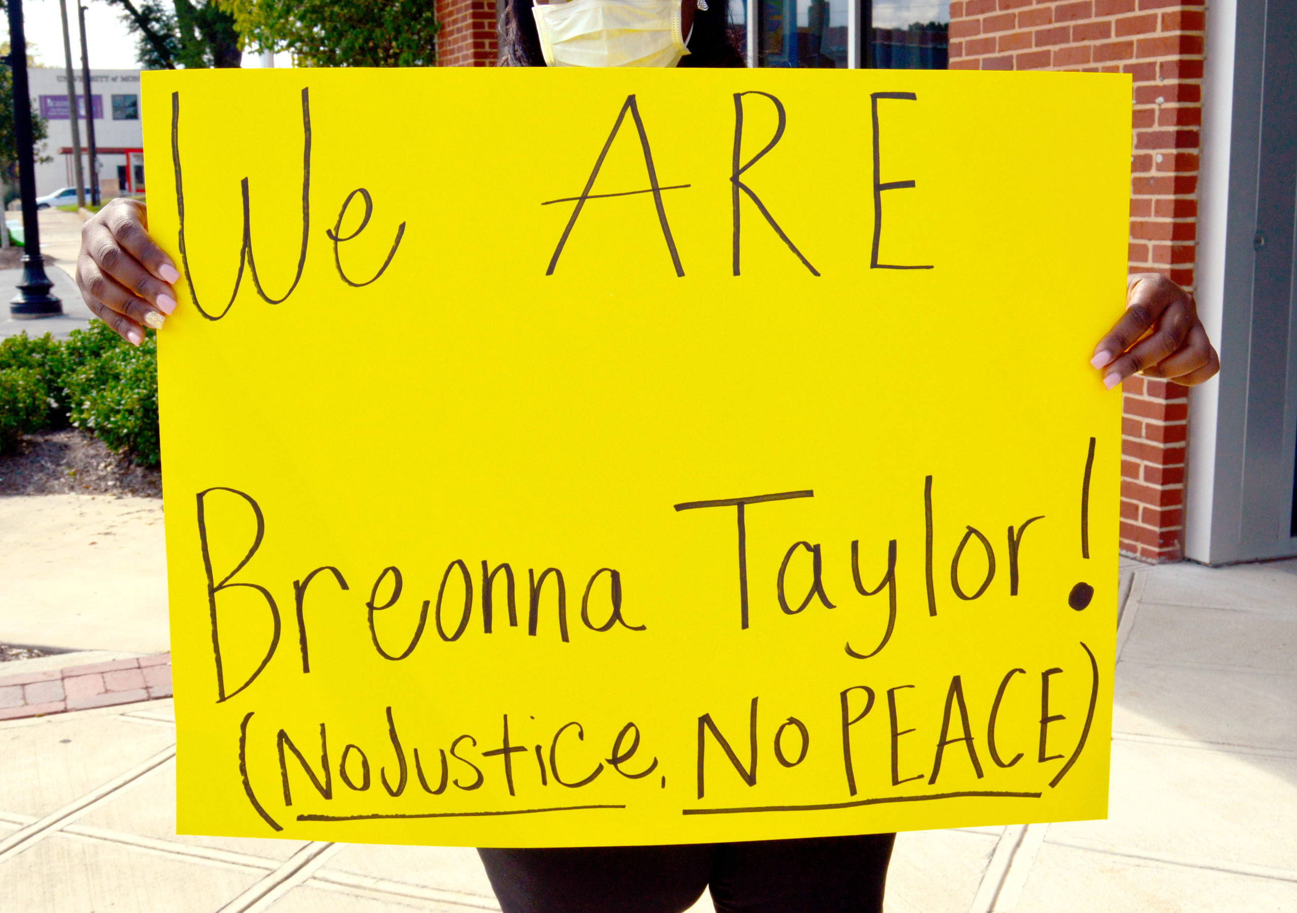 "A protestor in Montevallo holds up a sign that reads ""We are Breonna Taylor! No justice no peace."""