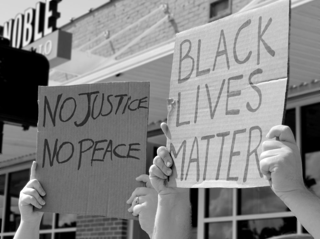 """Two protestors hold up signs reading """"No Justice No Peace"""" and """"Black Lives Matter."""""""
