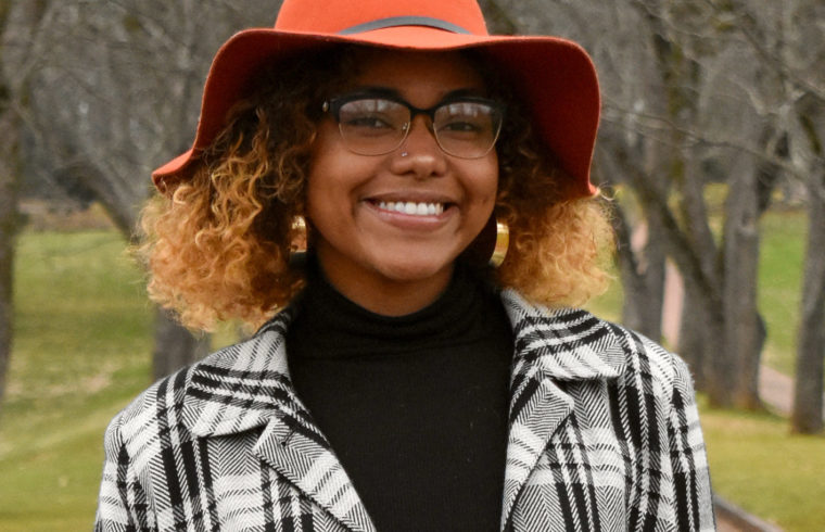 Image of Alexis Martinez, wearing a checkered flannel and red floppy hat.