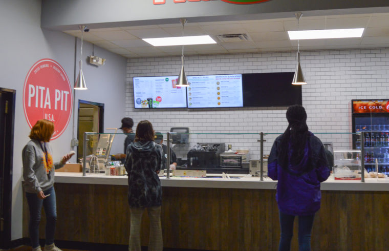 Picture of students in front of the counter for Pita Pit