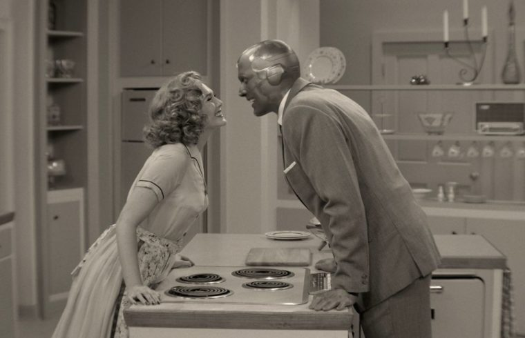Wanda and Vision smiling at each other in black and white across a counter top.