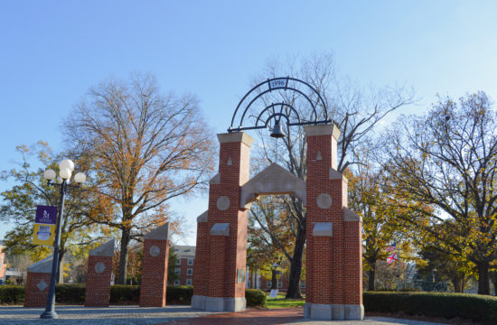 Brick archway with trees in the background